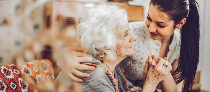 Infirmière qui enlace une personne âgée