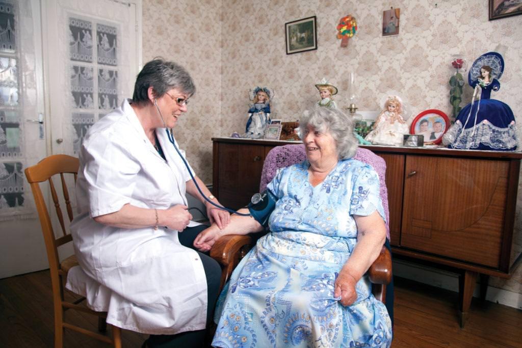 Une infirmière prend la tension d'une personne âgée. Elles sont toutes les deux assises.