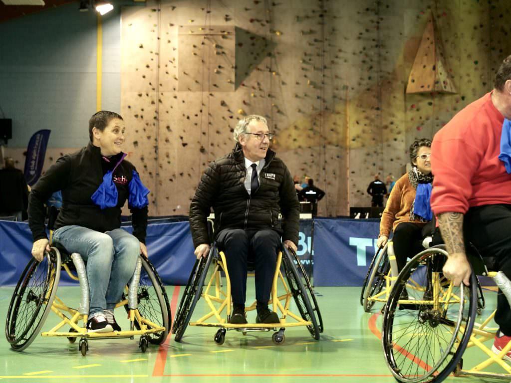 Groupe de personnes en fauteuil roulant en train de jouer au basket