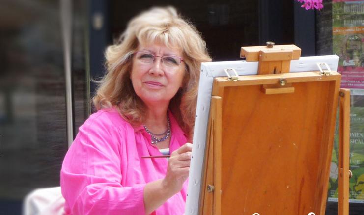 Femme blonde avec gilet rose en train de peindre sur un chevalet.