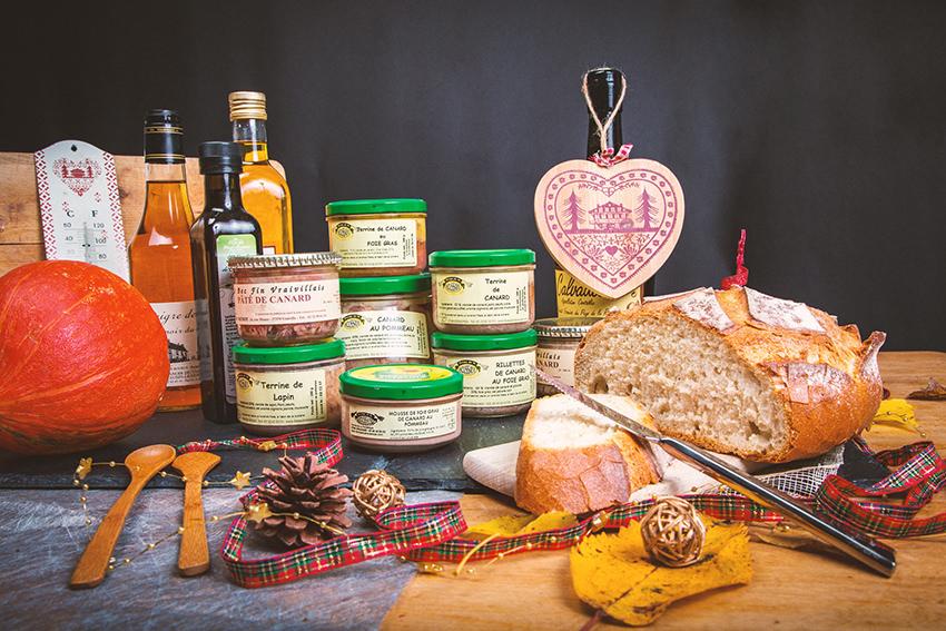 Ensemble de produits fermiers avec du pain, un potimaron, des pots de paté, des bouteilles d'huile, un couteau à pain, des couverts en bois, une planche à découper, des pommes de pin