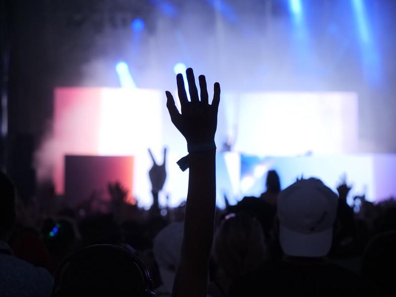 Une main levée au milieu d'une foule devant une scène