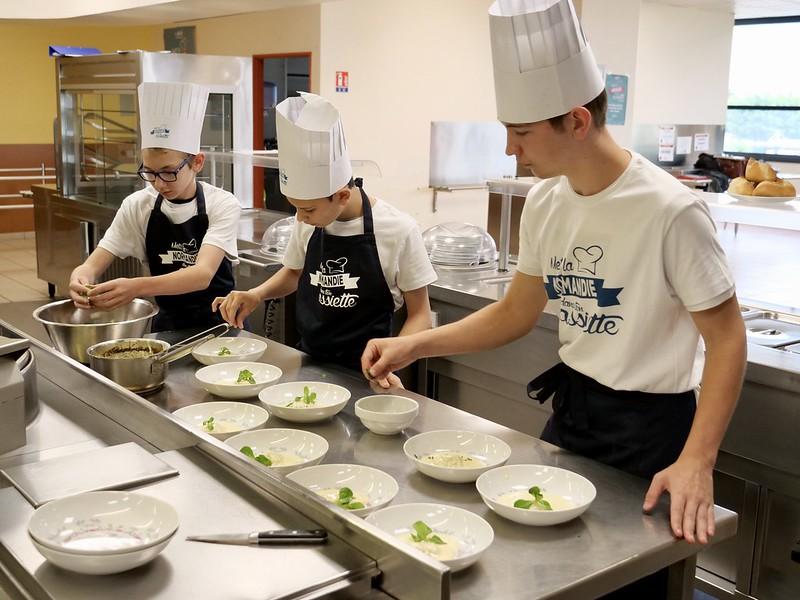 Trois jeunes en train de garnir des assiettes