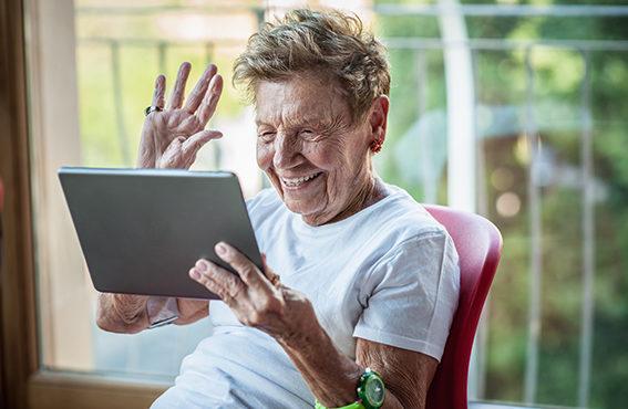 Femme âgée faisant un signe de la main devant une tablette