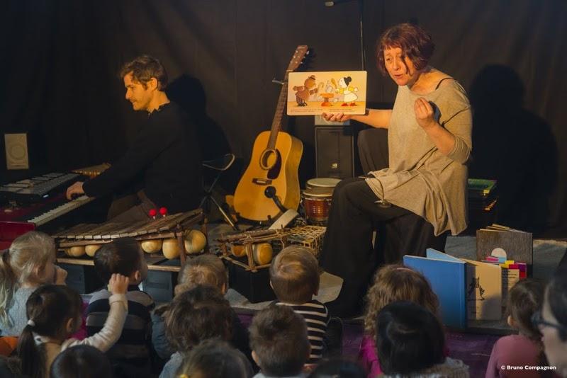 Conteuse avec un livre devant un groupe d'enfant