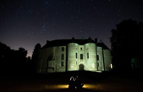 Chateau d'harcourt eclairé avec deux personnes en ombre devant