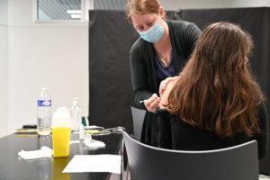femme avec un masque en train de vacciner une personne