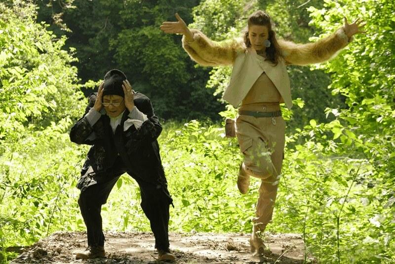 une femme levant les bras et un homme courbé se tenant la tête