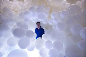 charle petillon au milieu de centaine de ballons blancs