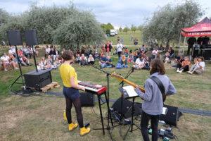 Groupe de musique en plein air devant un public assis dans l'herbe