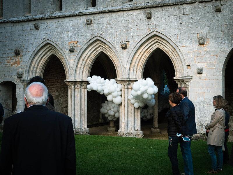 Groupe de personne devant des arcades d'abbaye et un ensemble de ballons blancs