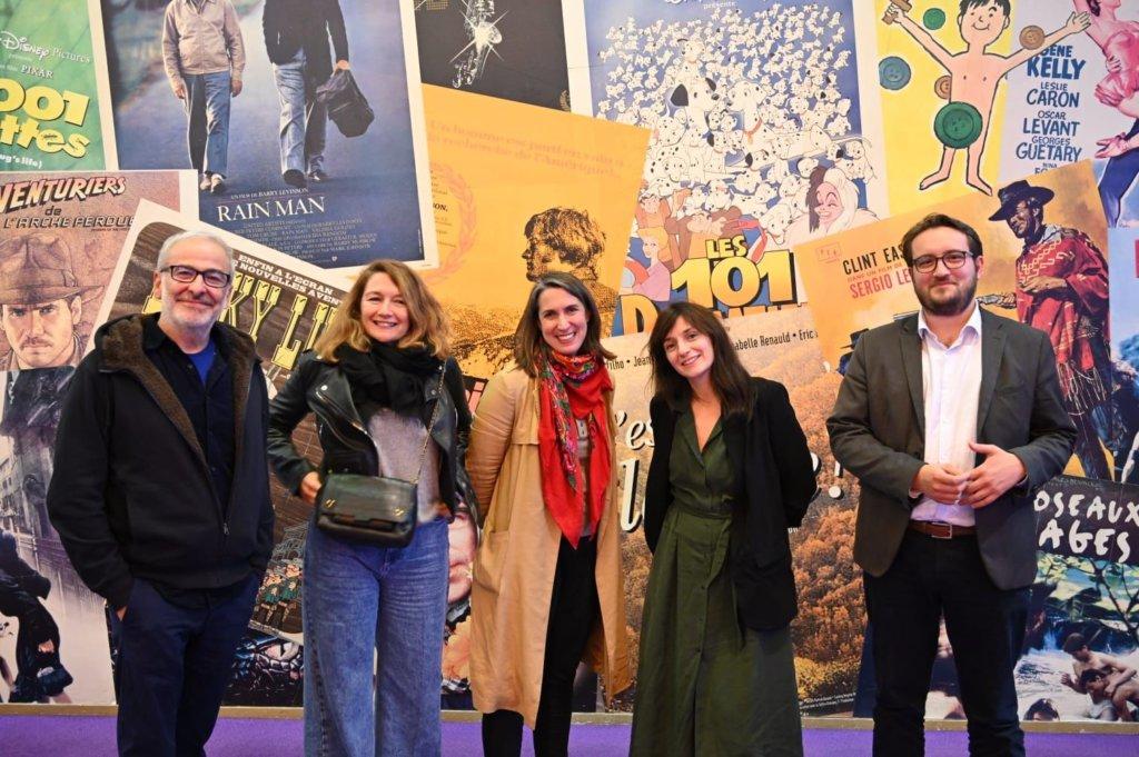 5 personnes devant des affiches de cinéma
